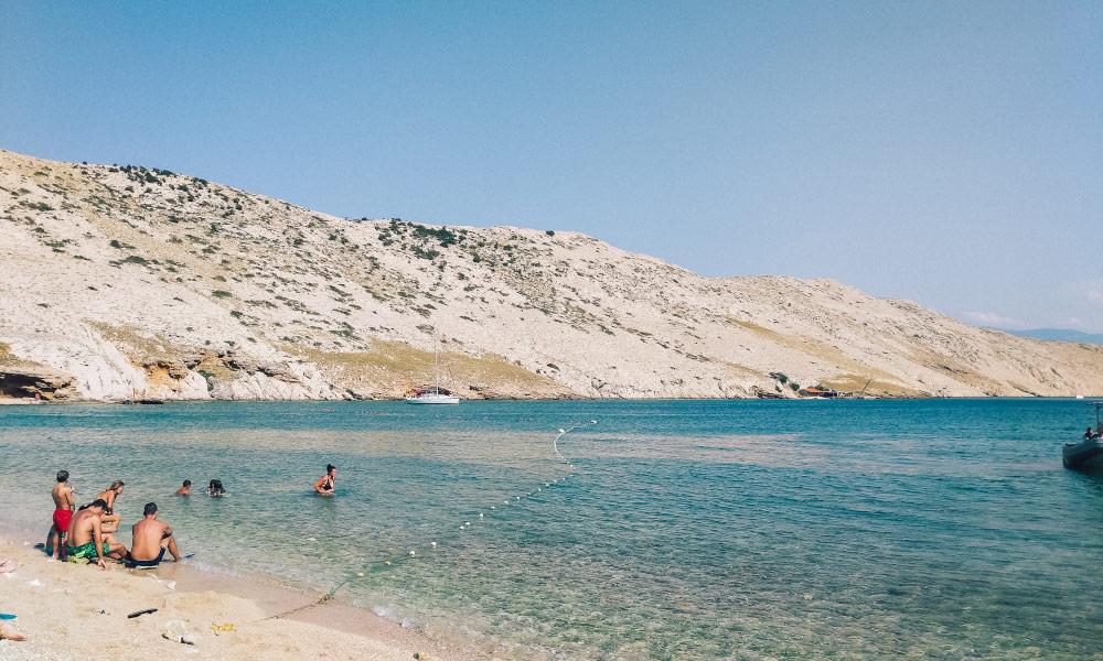 People enjoying the calm waters of Vela Luka beach
